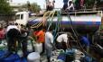 Diariamente, indianos se aglomeram para conseguir água distribuída pelo governo em carros pipa Foto: DOMINIQUE FAGET / AFP