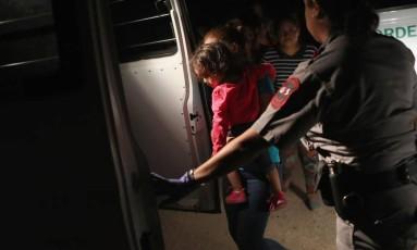 Mãe e filha que tentavam atravessar a fronteira para pedir asilo são levadas sob custódia perto da fronteira dos EUA com o México Foto: AFP/ John Moore