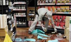 Empregado recolhe vidros e garrafas que caíram por causa do território em Osaka Foto: STR / AFP