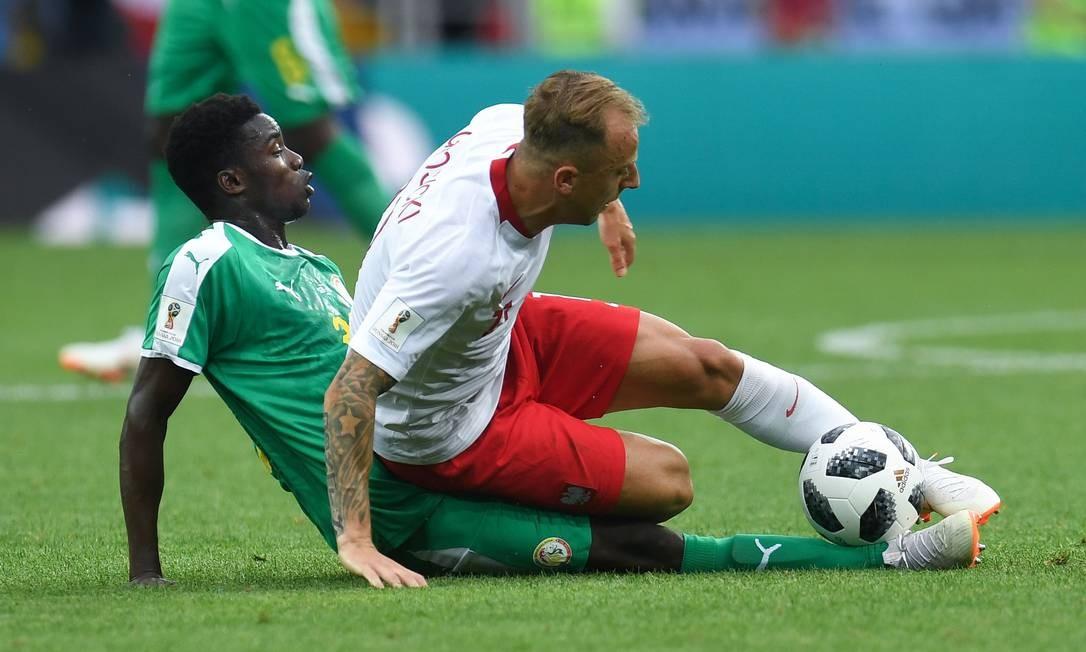 No combate direto, melhor para o defensor senegalense. Koulibaly (esquerda) desarma o atacante polonês Kamil Grosicki durante a partida Foto: PATRIK STOLLARZ / AFP