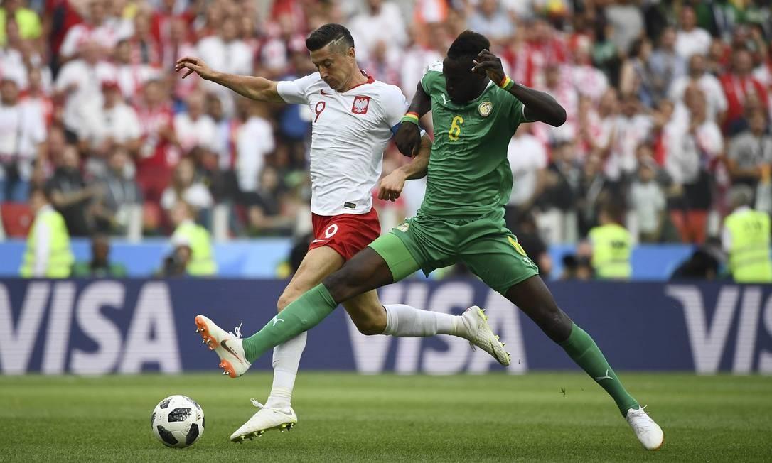 Craque da seleção da Polônia, Lewandowski (esquerda) passou zerado na primeira partida dos poloneses na Copa do Mundo. O atacante foi perseguido por todos os lados do campo pelos defensores senegalenses Foto: FRANCK FIFE / AFP