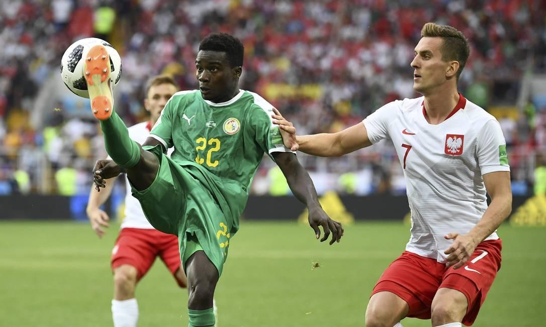 O lateral-direito Moussa Wague (esquerda) controla a bola e contém o ataque polaco, avançado com Milik (camisa 7) Foto: FRANCK FIFE / AFP