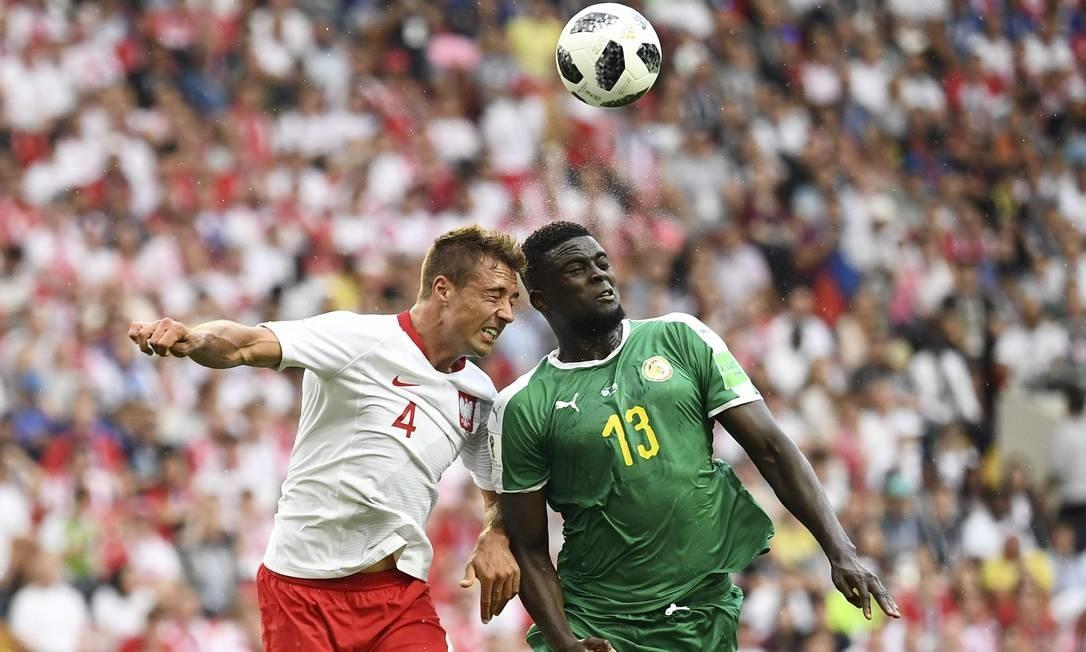 O brasileiro naturalizado polonês, Thiago Cionek (esquerda) e o meia Alfred N'Diaye de Senegal disputam bola pelo alto. O brasileiro marcou contra o primeiro gol da partida, abrindo o placar para os africanos Foto: FRANCK FIFE / AFP
