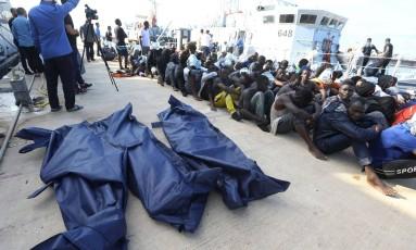 Dezenas de migrantes resgatados na costa líbia sentam-se junto a corpos de pessoas que morreram na tentativa de travessia à Europa Foto: MAHMUD TURKIA / AFP/18-6-2018