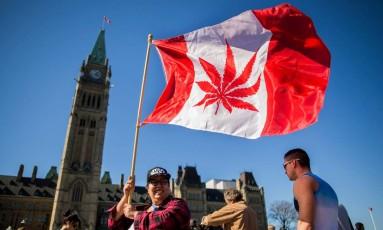 Mulher segura uma bandeira canadense onde se vê uma folha de maconha, em frente ao Parlamento, em Ottawa Foto: Chris Roussakis / AFP