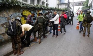 Militares revistam moradores na entrada das comunidades Babilônia e Chapéu Mangueira, no Leme Foto: Marcos de Paula / Agência O Globo