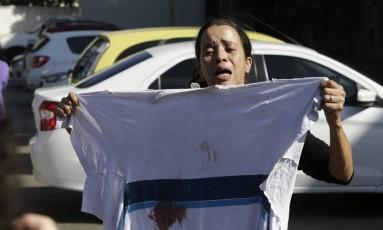 Bruna da Silva, mãe de Marcos Vinícius, exibe camisa que filho usava no momento em que foi baleado Foto: Antonio Scorza / Agência O Globo