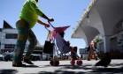 Mulher com criança em carrinho caminha até a Ponte de Santa Fé, ponto de verificação na fronteira dos EUA com o México Foto: AFP