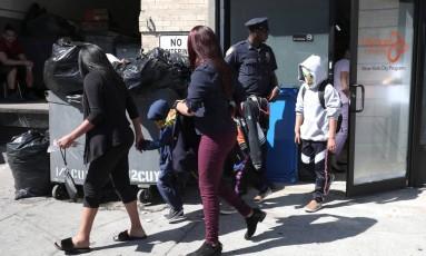 Crianças com os rostos cobertos por máscaras deixam o Centro Cayuga, em Nova York, que abriga crianças imigrantes separadas de suas famílias Foto: MIKE SEGAR / REUTERS