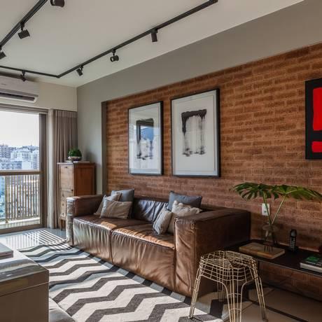 Sala. De Leandro Neves, com revestimento de tijolinho, sofá de couro e iluminação em trilhos Foto: Divulgação