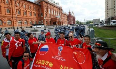 Um grupo de turistas chineses posa com uma bandeira de apoio à Rússia na Copa do Mundo Foto: GLEB GARANICH / REUTERS