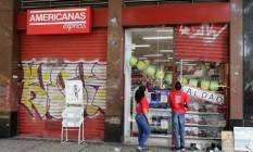 Funcionários fecham porta das Lojas Americanas após assalto Foto: Antônio Scorza / Agência O Globo