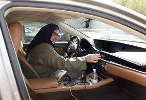 Recém-licenciada, Reem Farahat se prepara para um serviço de transporte ao cliente usando seu carro na capital saudita Foto: FAYEZ NURELDINE / AFP
