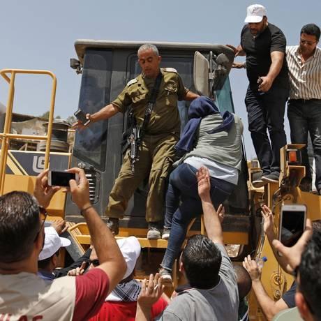 Manifestantes palestinos tentam impedir trator israelense de demolir povoado beduíno de Khan al-Ahmar, na Cisjordânia ocupada Foto: AHMAD GHARABLI / AFP