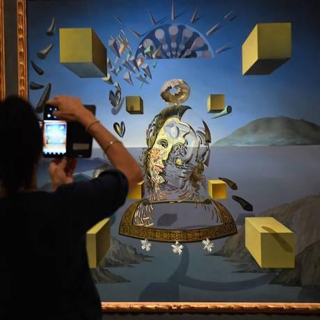 Uma visitante fotografa a tela 'Galatea in creation, 1954', que integra a mostra 'Gala Salvador Dali' Foto: LLUIS GENE / AFP