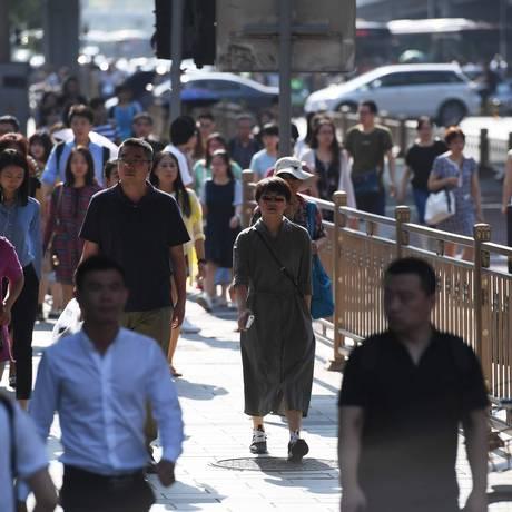 Chineses caminham em rua central de Pequim. Foto: Greg Baker/AFP