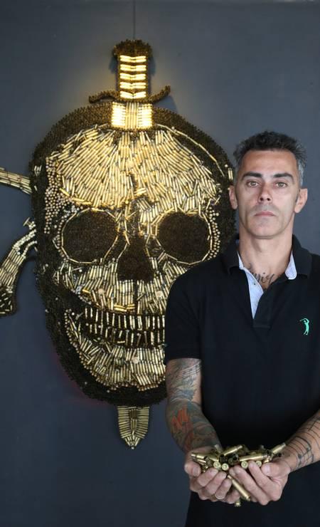 O artesão Rodrigo Camacho mostra as cápsulas utilizadas no painel do Bope Foto: Pedro Teixeira / Agência O Globo