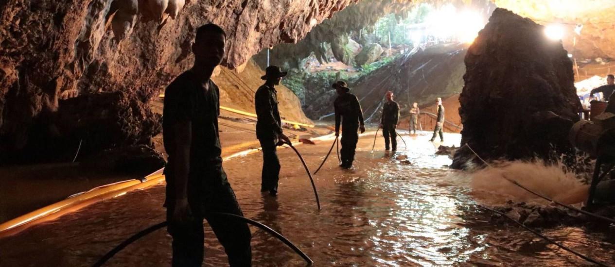 Integrantes das equipes de resgate em área inundada da caverna onde os 12 meninos de uma equipe de futebol e seu treinador estão presos na Tailândia: primeiros devem ser resgatados do local ainda neste domingo Foto: AFP PHOTO / ROYAL THAI NAVY