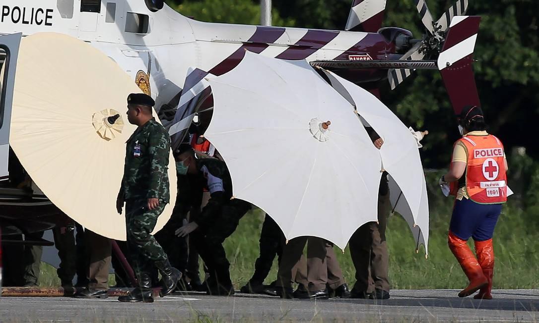 Forças de resgate usam guarda-sóis para preservar identidade de meninos resgatados Foto: ATHIT PERAWONGMETHA / REUTERS