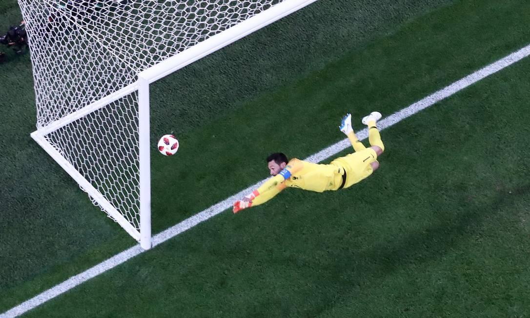 A imagem engana. O ângulo pode até aparentar que Lorris não conseguiu chegar na bola, mas ele defendeu esse chutaço de Alderweireld Foto: SERGIO PEREZ / REUTERS