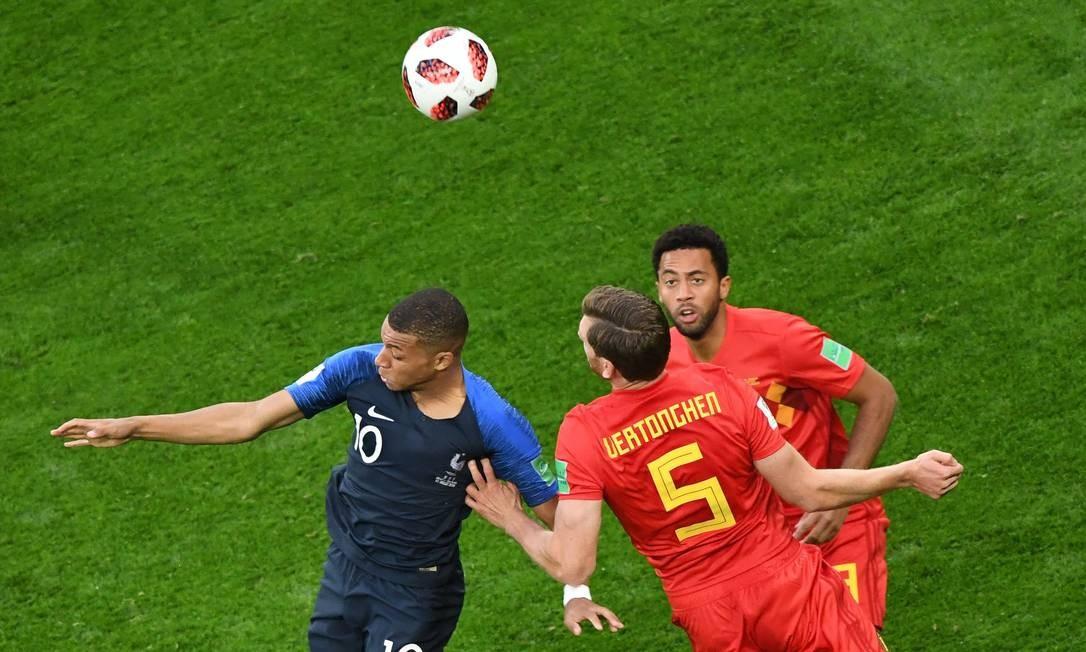O atacante Kylian Mbappe sobe para cabecear com o zagueiro belga Jan Vertonghen e o meia Moussa Dembele FRANCOIS XAVIER MARIT / AFP