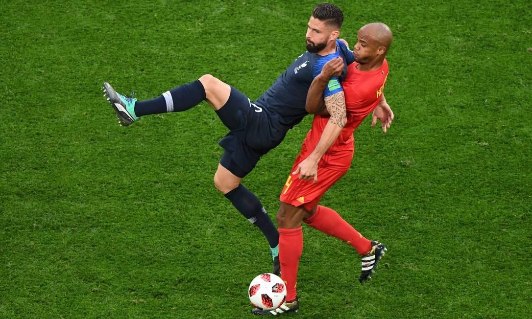 Olivier Giroud, atacante da seleção francesa, disputa a bola com o zagueiro Vincent Kompany, da Bélgica FRANCOIS XAVIER MARIT / AFP