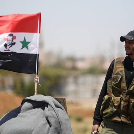 Soldado pró-Assad ao lado de bandeira síria com imagem de presidente, na província de Daraa, área recém conquistada Foto: OMAR SANADIKI / REUTERS
