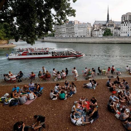 Pessoas sentadas às margens do Rio Sena em uma área transformada para o Paris Plages Foto: FRANCOIS GUILLOT / AFP