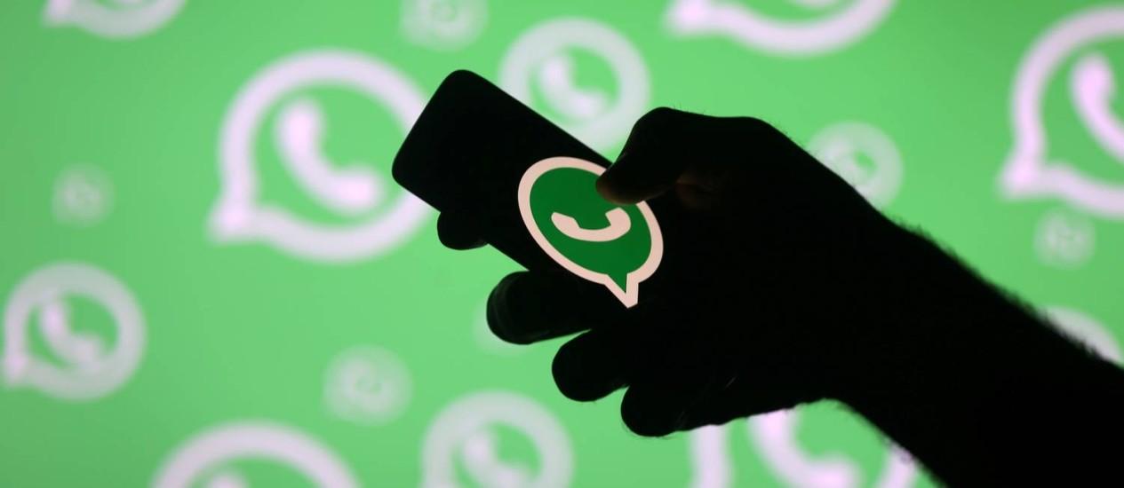 Pessoa segura o telefone celular em frente a uma tela com o logos do Whatsapp: aplicativo foi usado para disseminar acusações falsas que levaram à morte por linchamento de diversas pessoas na Índia Foto: REUTERS/Dado Ruvic