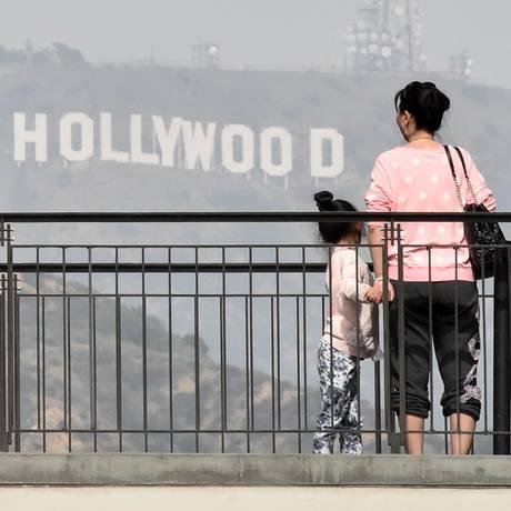 Turistas fotografam o letreiro de Hollywood, instalado em 1923 pelo mercado imobiliário de Los Angeles Foto: MLADEN ANTONOV / AFP