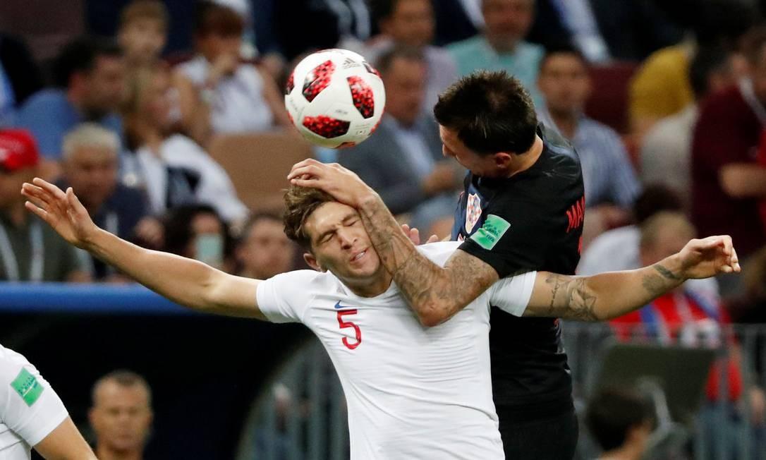 O croata Mario Mandzukic em disputa de bola com o inglês John Stones GRIGORY DUKOR / REUTERS