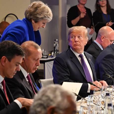 Ao lado de colegas e chefes de Estado e de governo, Trump vê chegada de Theresa May Foto: GEERT VANDEN WIJNGAERT / AFP