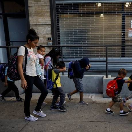 Crianças cobrem o rosto ao chegar em abrigo para menores imigrantes separados dos pais, em Nova York Foto: REUTERS/Brendan McDermid
