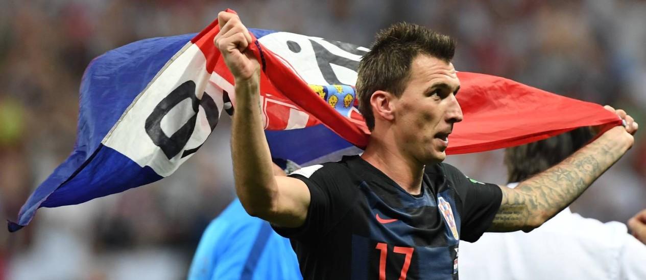 Mario Mandzukic estende a bandeira croata após a vitória sobre a Inglaterra Foto: YURI CORTEZ / AFP