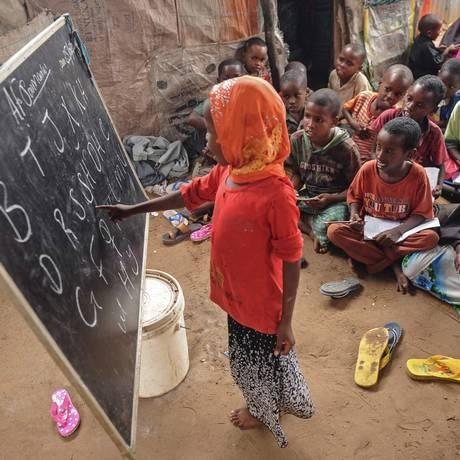 Criança aprende o alfabeto em uma escola improvisada no interior da Somália: falta de instrução formal é desafio para meninas no mundo inteiro Foto: MOHAMED ABDIWAHAB / AFP/25-6-2018