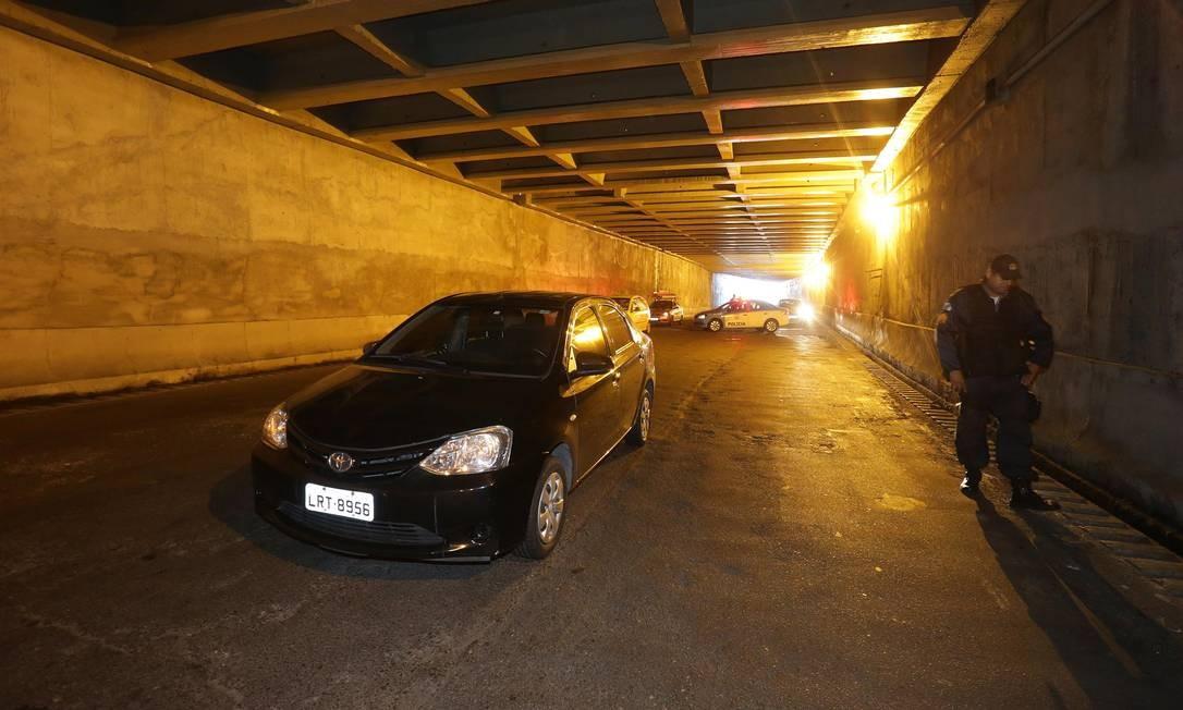 Um PM ao lado do carro da vítima, no Túnel Noel Rosa Foto: Marcio Alves / Agência O Globo