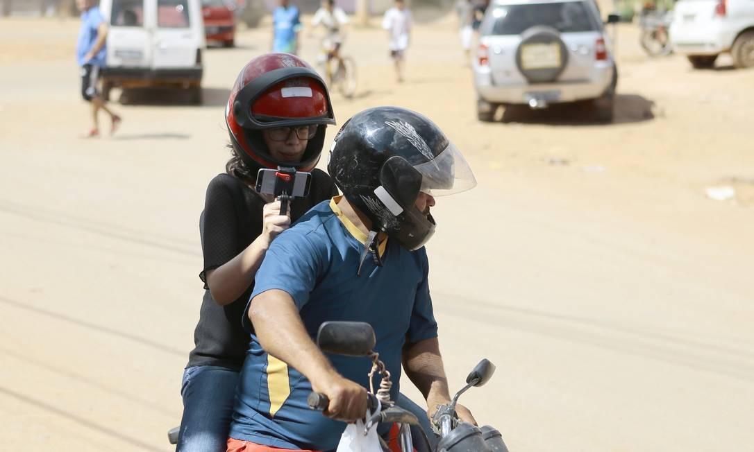 A repórter Renata Mariz saindo de moto taxi para filmar as ruas Foto: Jorge William / Agência O Globo