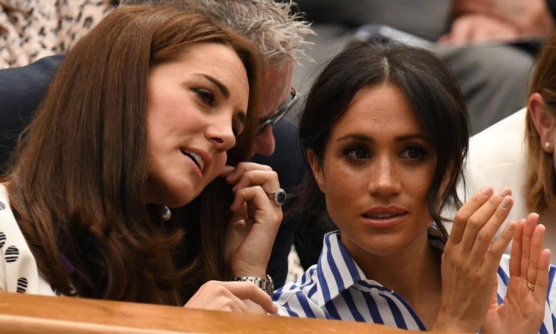 Kate e Meghan aproveitam o jogo para botar a conversa em dia Foto: OLI SCARFF / AFP