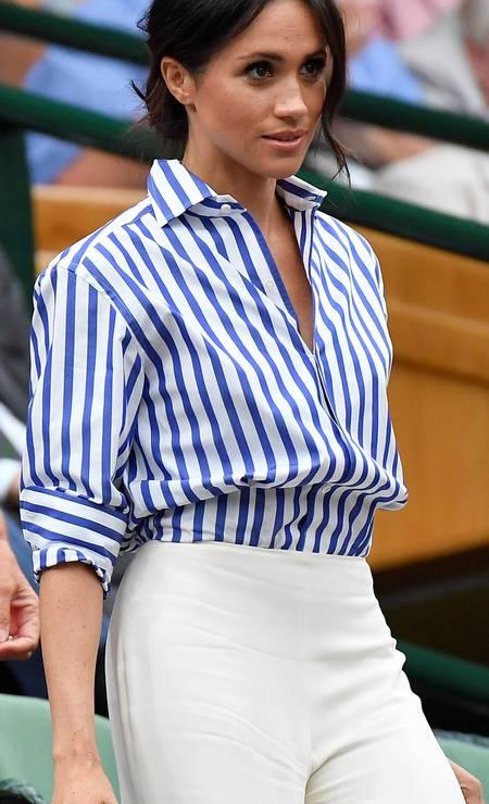 A duquesa de Sussex de camisa social e calça branca, ambas da americana Ralph Lauren Foto: TOBY MELVILLE / REUTERS