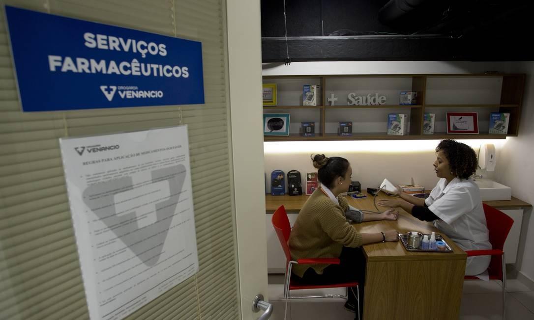 Consulta. Farmacêutica Tatiane Machado da Silva examina cliente na megaloja da Drogaria Venâncio em Copacabana Foto: / Márcia Foletto