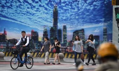 Pessoas atravessam a rua em Pequim, perto de local de nova construção. Foto: Greg Baker/AFP