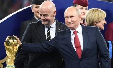 O presidente da Rússia, Vladimir Putin, toca a taça da Copa sob olhares do presidente da Fifa, Gianni Infantino Foto: JEWEL SAMAD / AFP