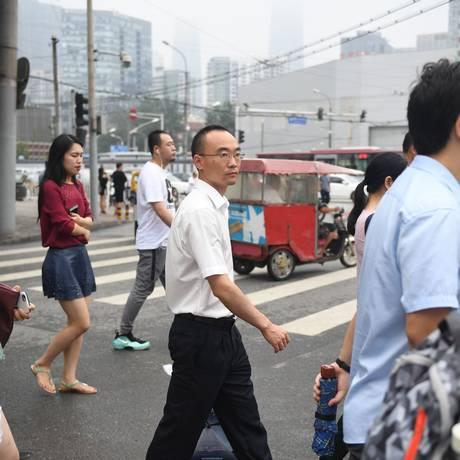 Pedestres atravessam a rua em Pequim. Foto: Greg Baker/AFP