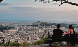 Jovens conversam num jardim com vista para Atenas, com a Acrópole em destaque Foto: LOUISA GOULIAMAKI / AFP