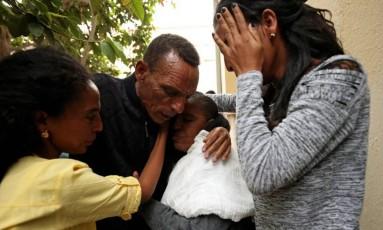 Addisalem Hadgu se emociona ao reencontrar esposa e filhas após 18 anos separados Foto: TIKSA NEGERI / REUTERS