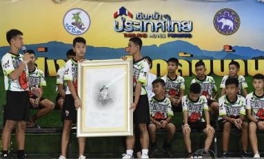 O treinador Ekkapol Chantawong e 12 jovens resgatados da caverna na Tailândia, em Chiang Rai, após liberação do hospital. Eles prestam homenagem ao fuzileiro naval Saman Kunan, que morreu durante a operação Foto: LILLIAN SUWANRUMPHA / AFP