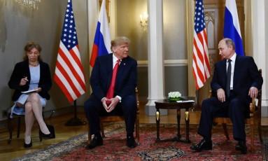 Em cúpula na Finlândia, Donald Trump e Vladimir Putin conversam; ao canto, intérprete faz anotações Foto: BRENDAN SMIALOWSKI / AFP