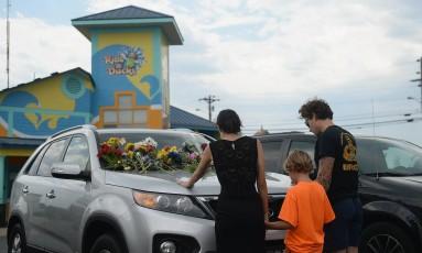 Uma família presta homenagem aos mortos no naufrágio em um lago do Missouri. Muitas pessoas deixaram flores nos carros estacionados no píer Foto: Michael Thomas / AFP