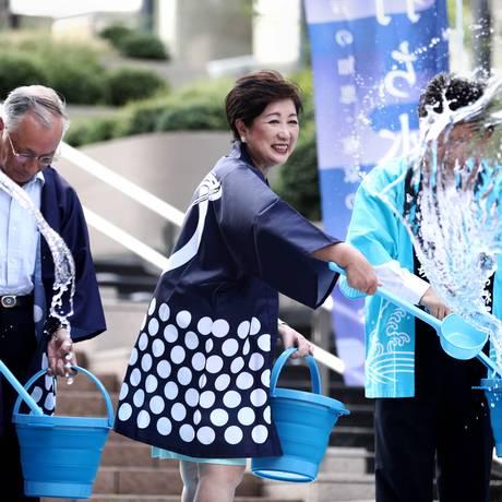 A governadora de Tóquio, Yuriko Koike, joga água no chão seguindo a tradição conhecida como Uchimizu para combater o calor Foto: BEHROUZ MEHRI / AFP