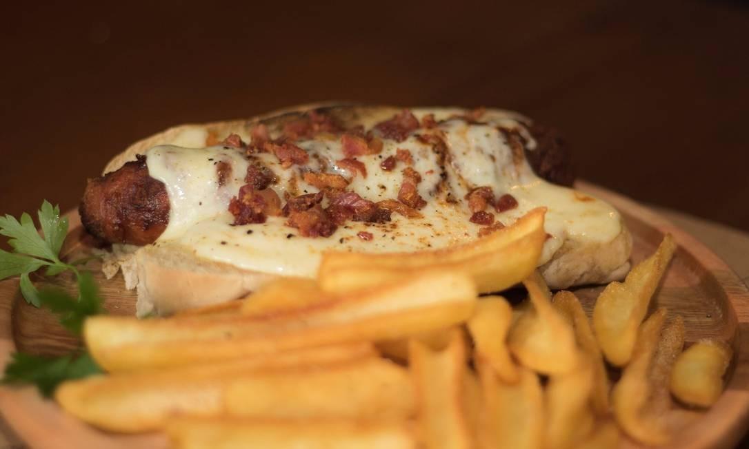 Urbanito. A linguiça artesanal do hot dog de bacon a vida (R$ 30) é de pernil e o sanduíche leva maionese de páprica e alho, queijo derretido, barbecue e farofa de bacon no pao de malte, e ainda é servido com batata frita. Rua Joaquim Palhares 513, Tijuca Foto: Divulgação